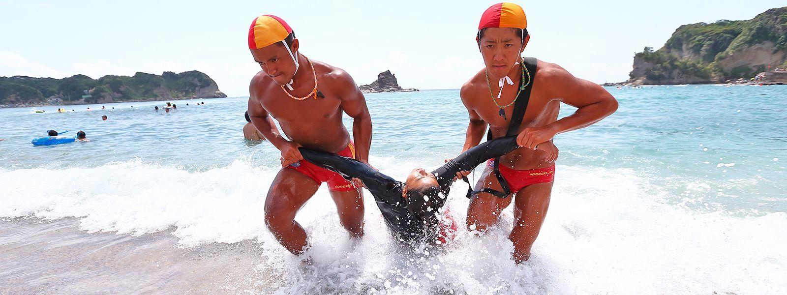 ライフセーバーが救急患者を海から引き上げている